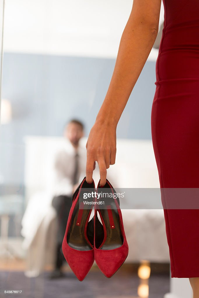 Woman Holding High Heels With Man In Bedroom : Stock Photo