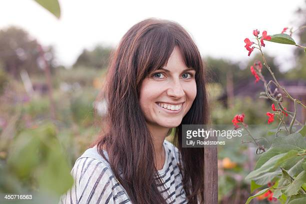 Woman holding hoe and smiling at allotment