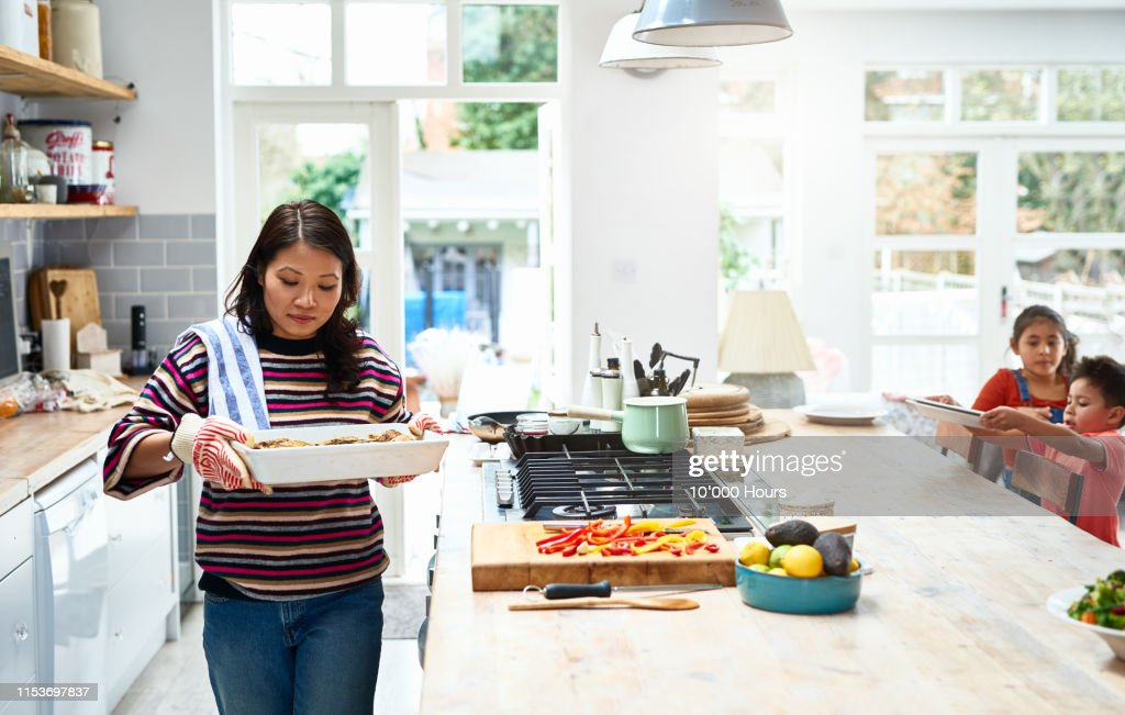 Woman holding hot casserole dish in kitchen : Stock Photo