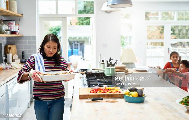 woman holding hot casserole dish in kitchen - four people photos et images de collection