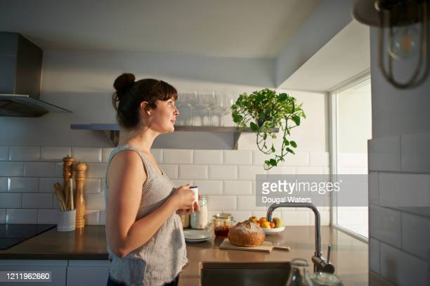 woman holding hot drink and looking out of kitchen window. - rêvasser photos et images de collection