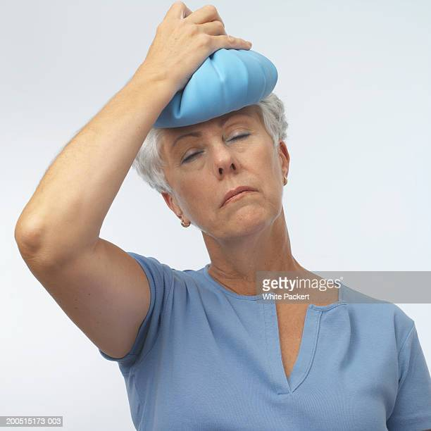 Woman holding hot water bottle on head, head and shoulders