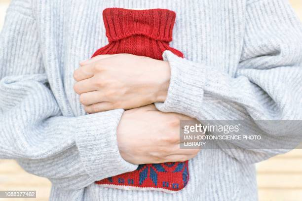 woman holding hot water bottle - pms stock pictures, royalty-free photos & images