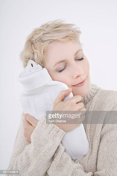 Woman holding hot water bottle, eyes closed