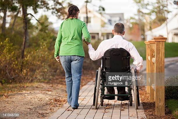 Frau, die Mann-hand, die auf einen Rollstuhl
