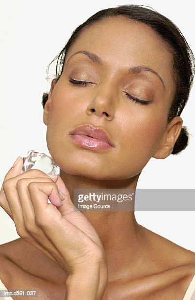 Woman holding ice cube on face