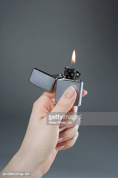 Woman holding illuminated cigarette lighter, close-up of hand