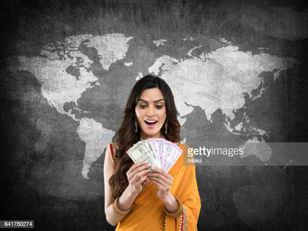 woman holding indian paper currency - indian currency stock photos and pictures