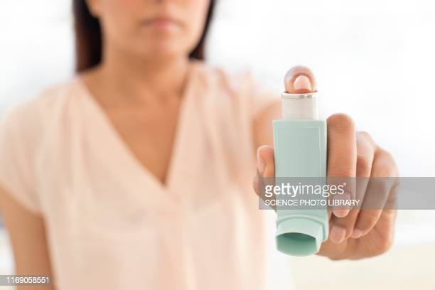 woman holding inhaler - asthma stock pictures, royalty-free photos & images