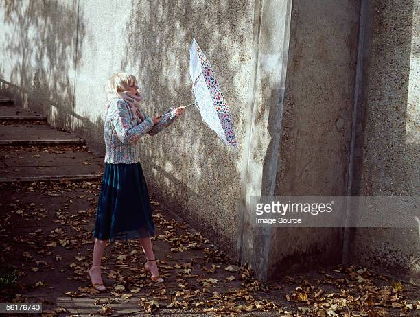 woman holding inside-out umbrella - inside out stock pictures, royalty-free photos & images