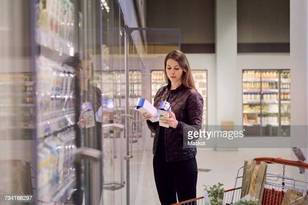 Woman holding juice boxes at refrigerated section in supermarket