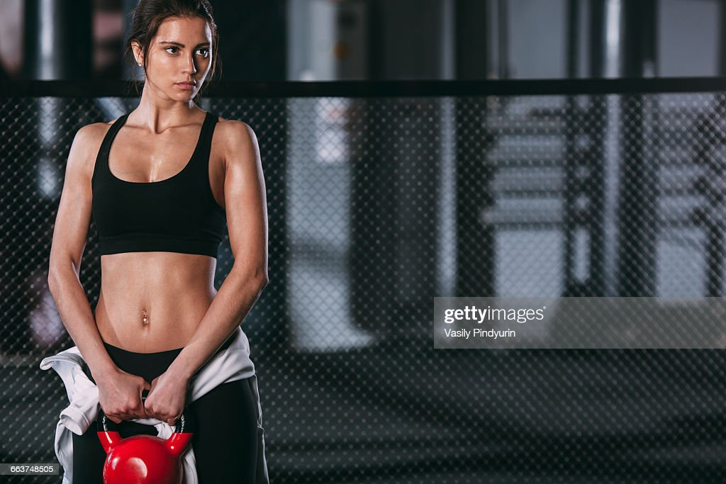 Woman holding kettlebell and standing against fence at gym : Stock Photo
