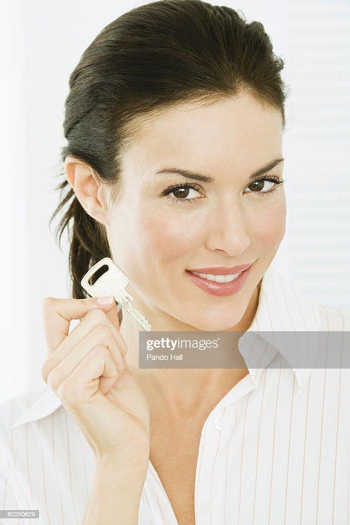 Woman holding key, smiling, portrait : Stock Photo