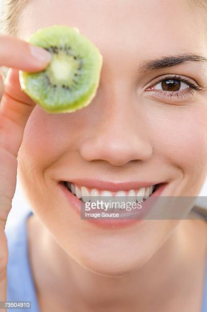 Woman holding kiwi fruit