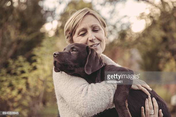 woman holding labrador retriever - einzelnes tier stock-fotos und bilder