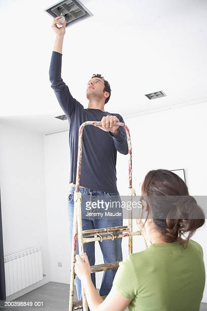 Woman holding ladder by man changing light bulb