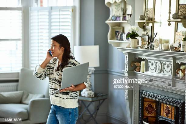 woman holding laptop and listening on smartphone - complaining stock pictures, royalty-free photos & images