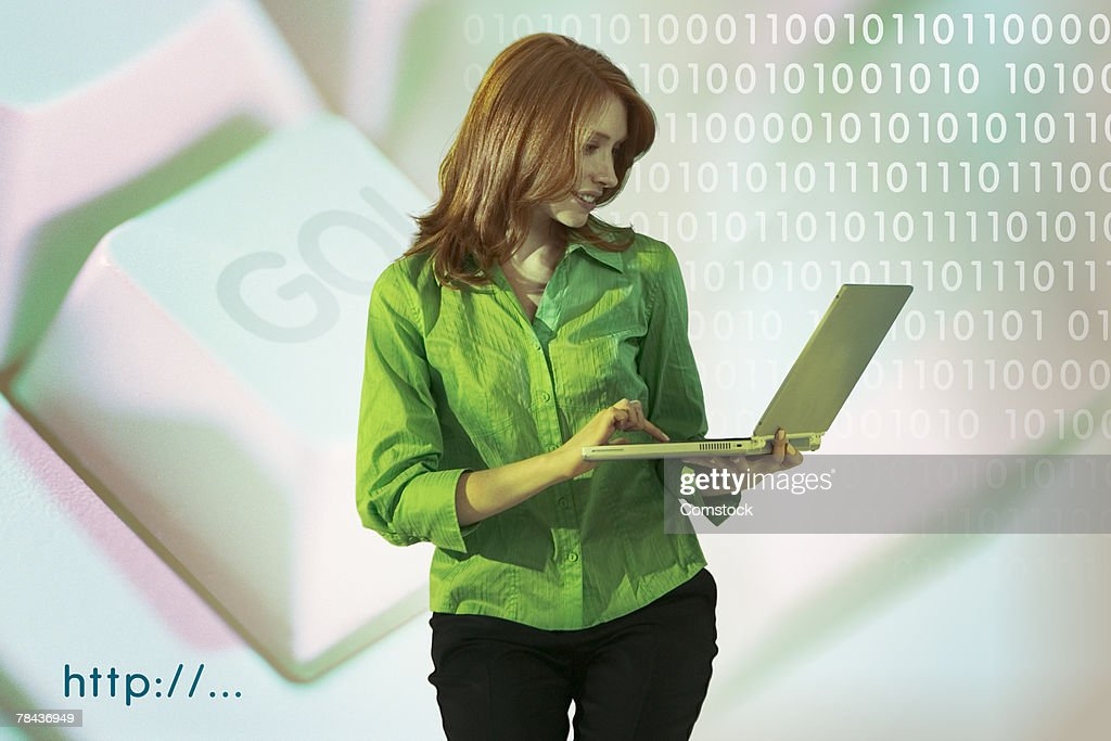 Woman holding laptop computer with binary code and go button : Stockfoto