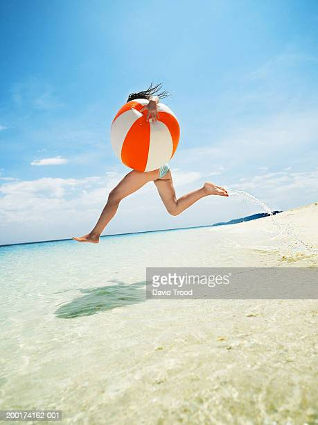 Woman holding large beach ball, in air above ocean, side view