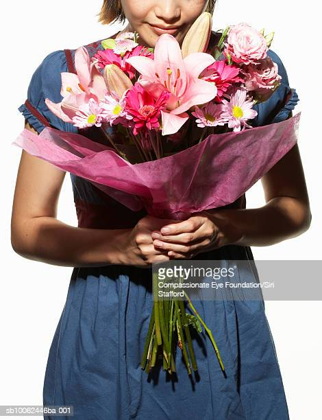 "woman holding large bouquet of flowers, mid section - ""compassionate eye"" stock pictures, royalty-free photos & images"