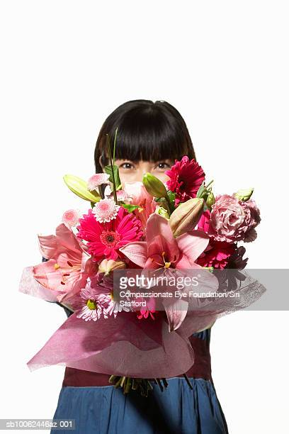 """woman holding large bouquet of flowers over face, portrait - """"compassionate eye"""" - fotografias e filmes do acervo"""