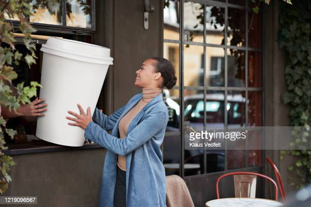 woman holding large disposable coffee cup at take away counter of cafe - large stock pictures, royalty-free photos & images