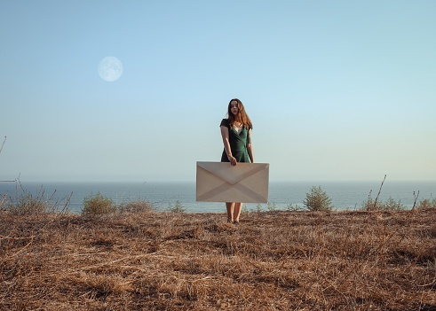 Woman Holding Large Envelope While Standing On Field Against Sea And Clear Sky - gettyimageskorea