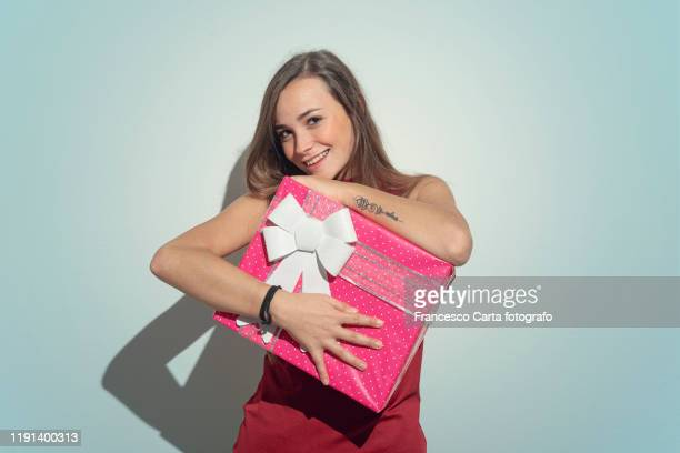 woman holding large present - donna bendata foto e immagini stock