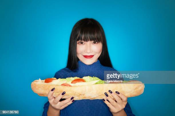 woman holding large sandwich - waist up stock pictures, royalty-free photos & images