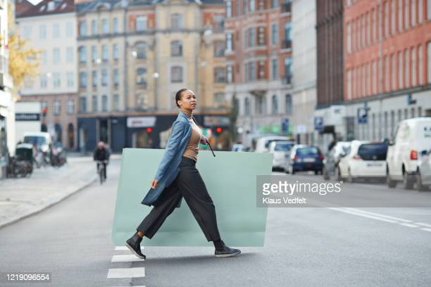 woman holding large shopping bag while walking on street in city - information overload stock pictures, royalty-free photos & images