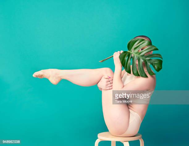 woman holding leaf in yoga pose - sexy figures stock pictures, royalty-free photos & images