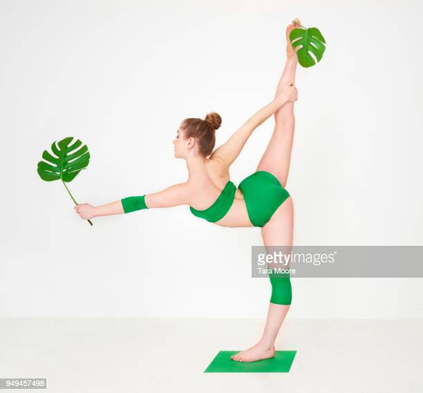 woman holding leaves in yoga pose