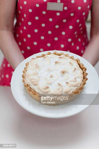 Woman holding lemon meringue pie