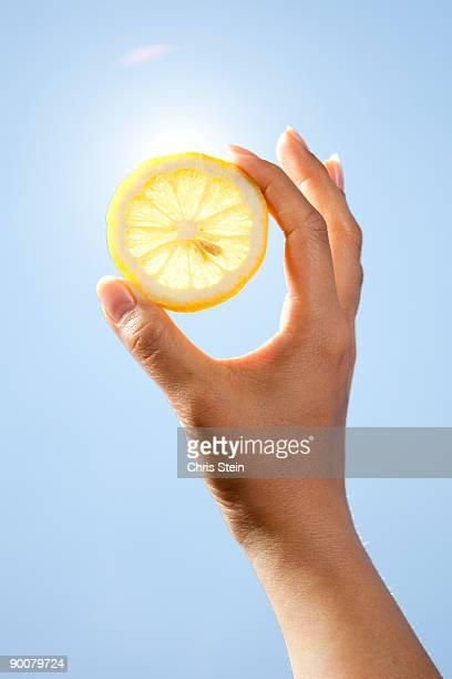 Woman holding lemon slice