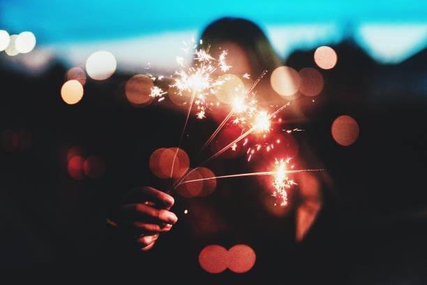 Woman Holding Lit Sparklers At Night