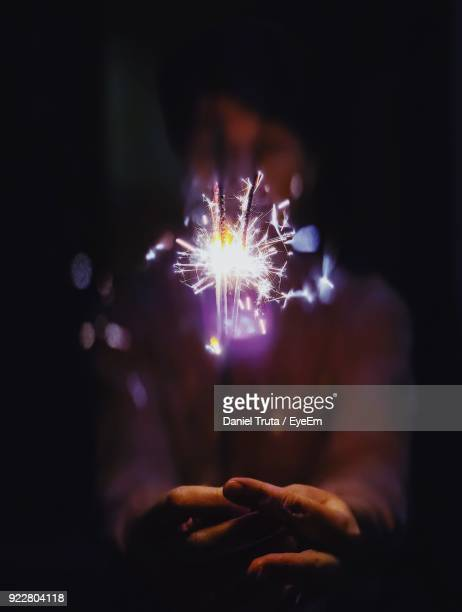woman holding lit sparklers at night - daniel funke stock-fotos und bilder