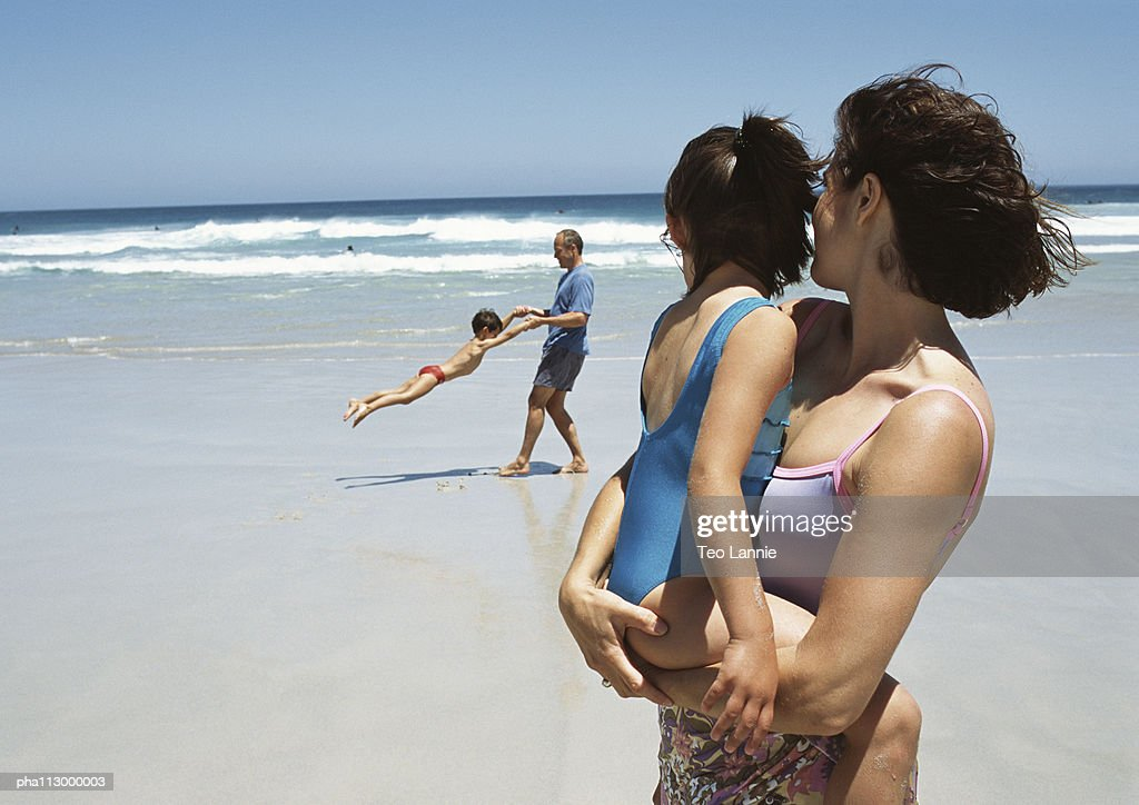 Woman holding little girl in arms in foreground on beach, man swinging little boy in background : ストックフォト
