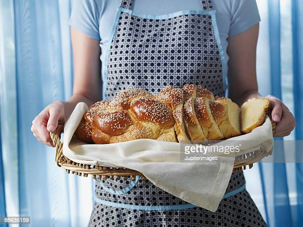 Woman holding loaf of sliced challah