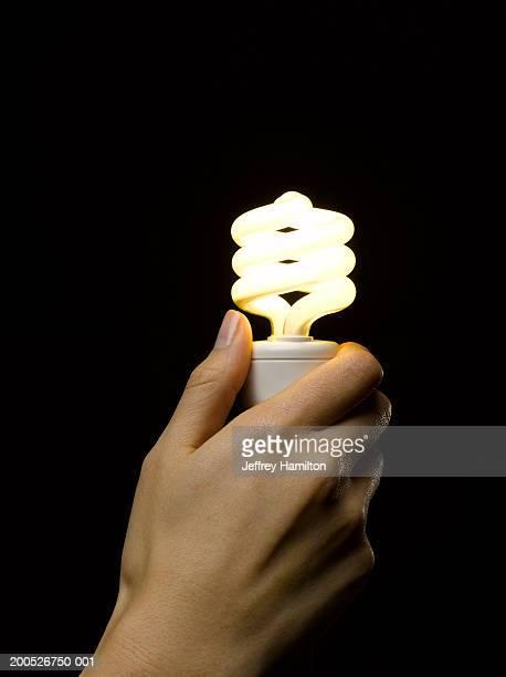 Woman holding low energy lightbulb against black background