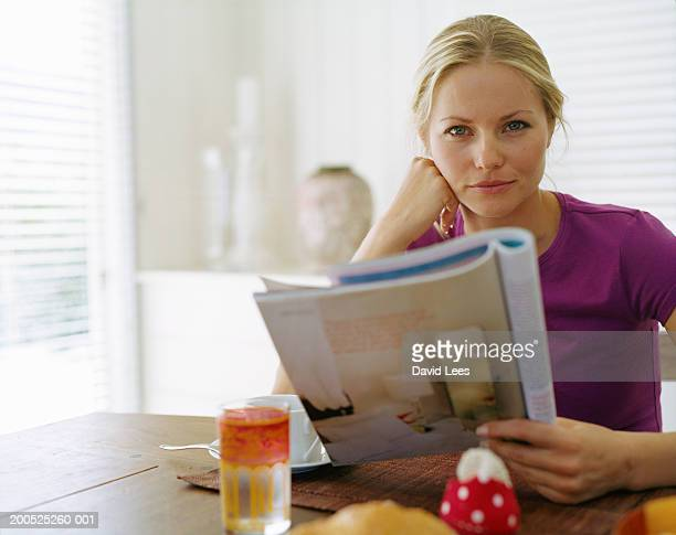 Woman holding magazine at table, portrait