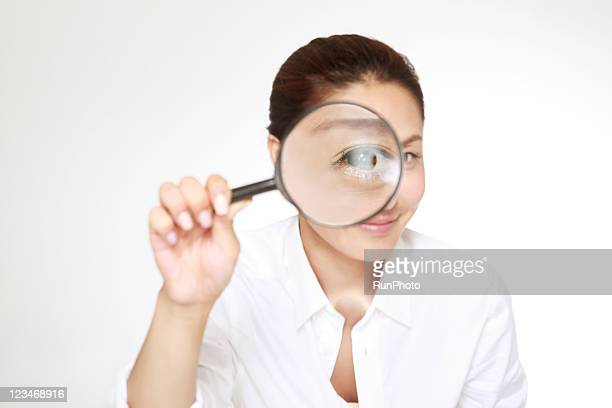 woman holding magnifying glass in front of eye