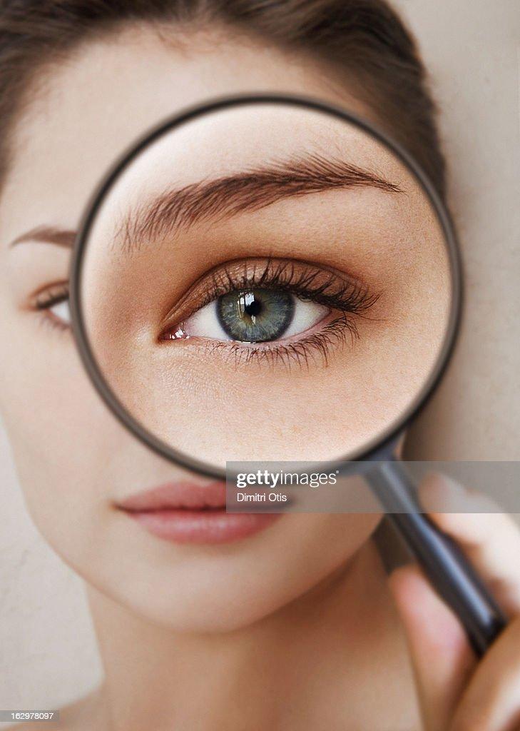 Woman holding magnifying glass in front of her eye : Bildbanksbilder