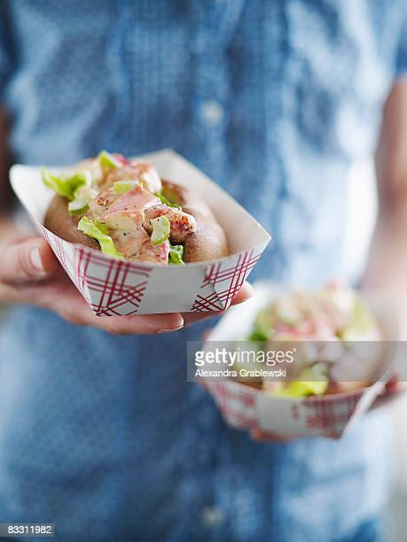 woman holding maine lobster roll - bun stock pictures, royalty-free photos & images