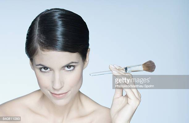 Woman holding make-up brush, portrait