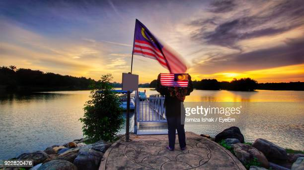 Woman Holding Malaysian Flag While Standing Against Lake During Sunset