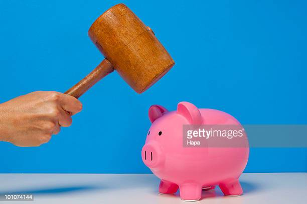Woman holding mallet over piggy bank