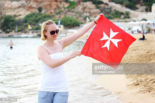 Woman holding Malta's red flag on the beach
