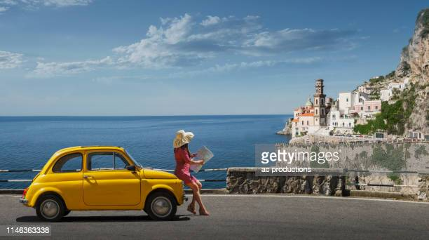 woman holding map leaning on yellow car in atrani, italy - italie photos et images de collection