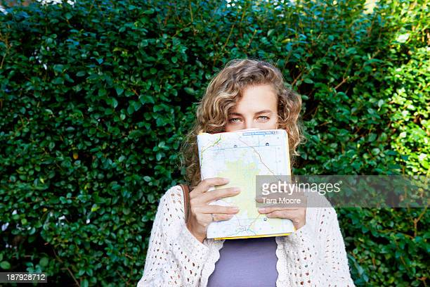 woman holding map over face