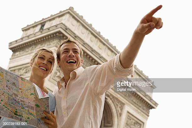 Woman holding map with man pointing, smiling, low angle view